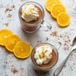 2 cups of hot chocolate with slices of orange and cream