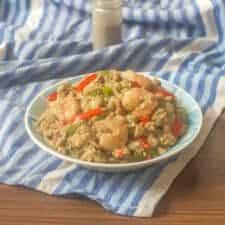 Delicious stir fried shrimp quinoa bowl on a blue cloth