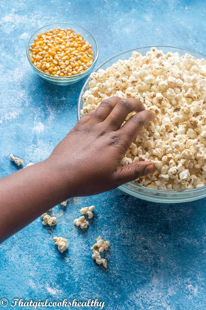 Hand reaching for some cinnamon sweet salted instant pot popcorn