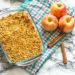 apple crisp in a pyrex next to red apples