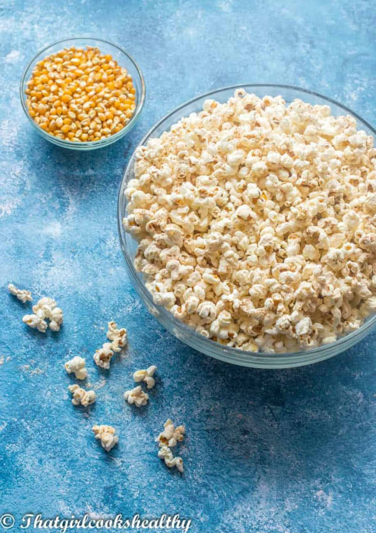 a big bowl of popcorn with kernels on the side