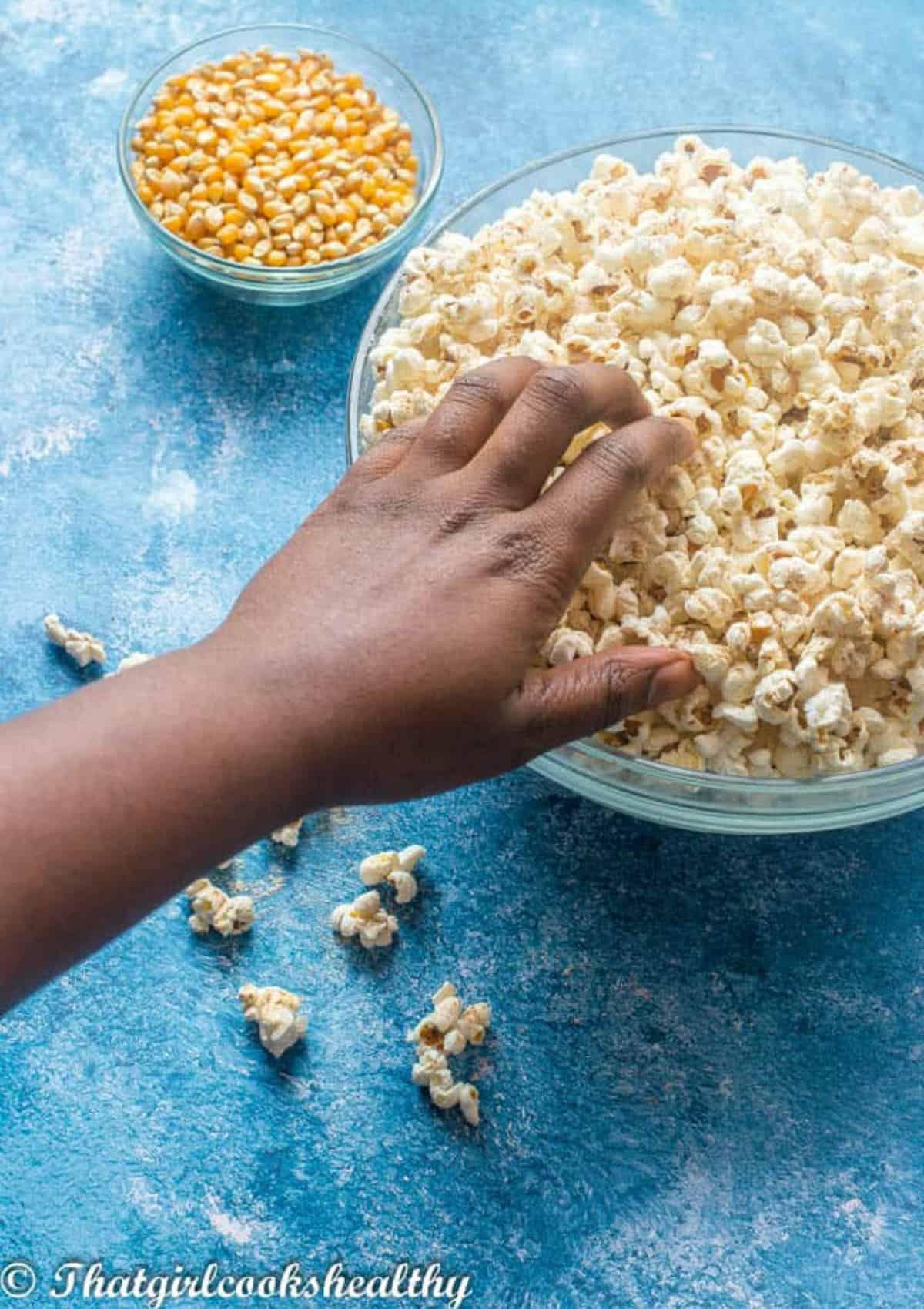 hand touching the popcorn
