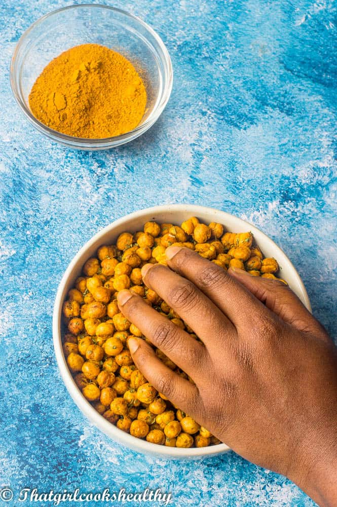 Curried air fryer chickpeas with hand hoovering over them