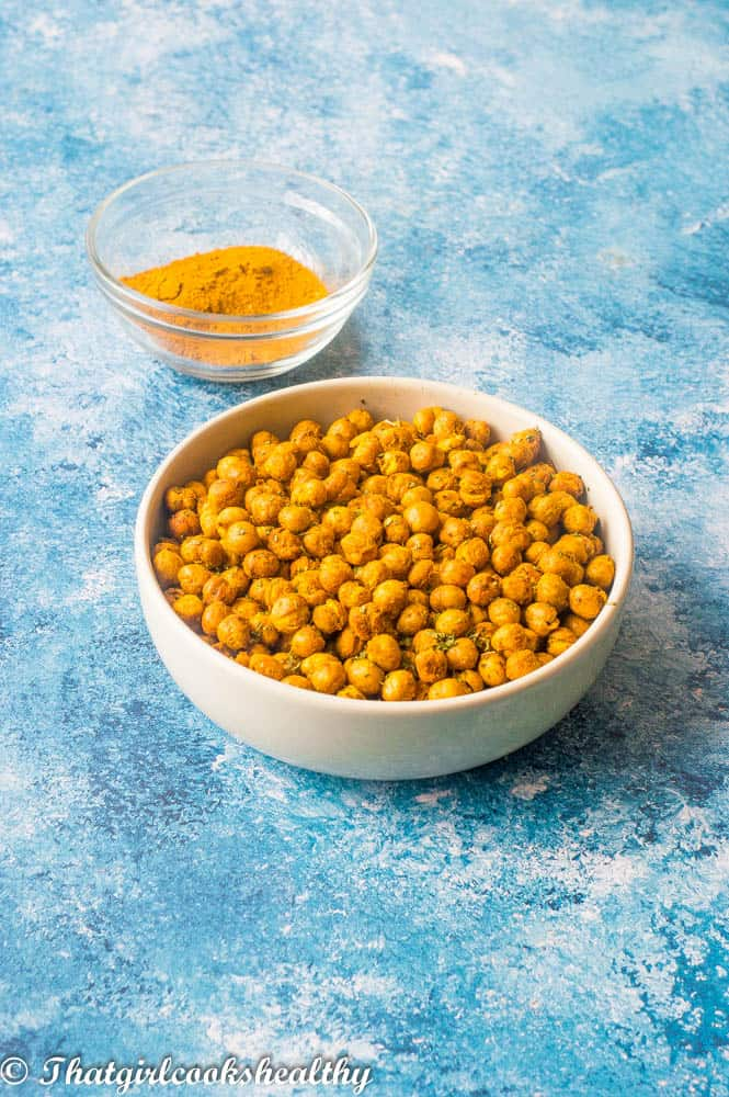 Curried air fryer chickpeas with curry powder in the background