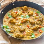 Pan of curried cod fish garnished with herbs