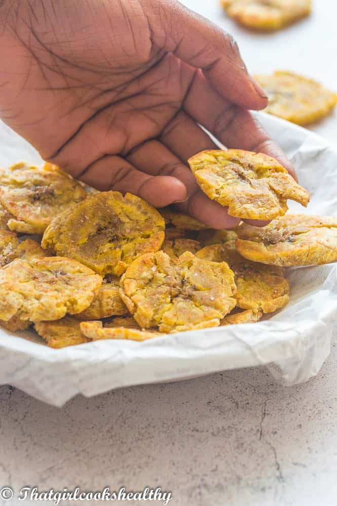 Hand picking up some tostones