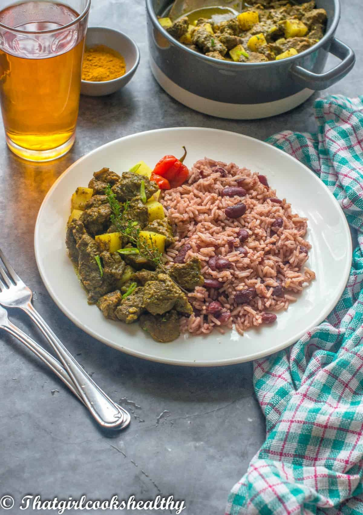 rice and peas with curry goat on a white plate