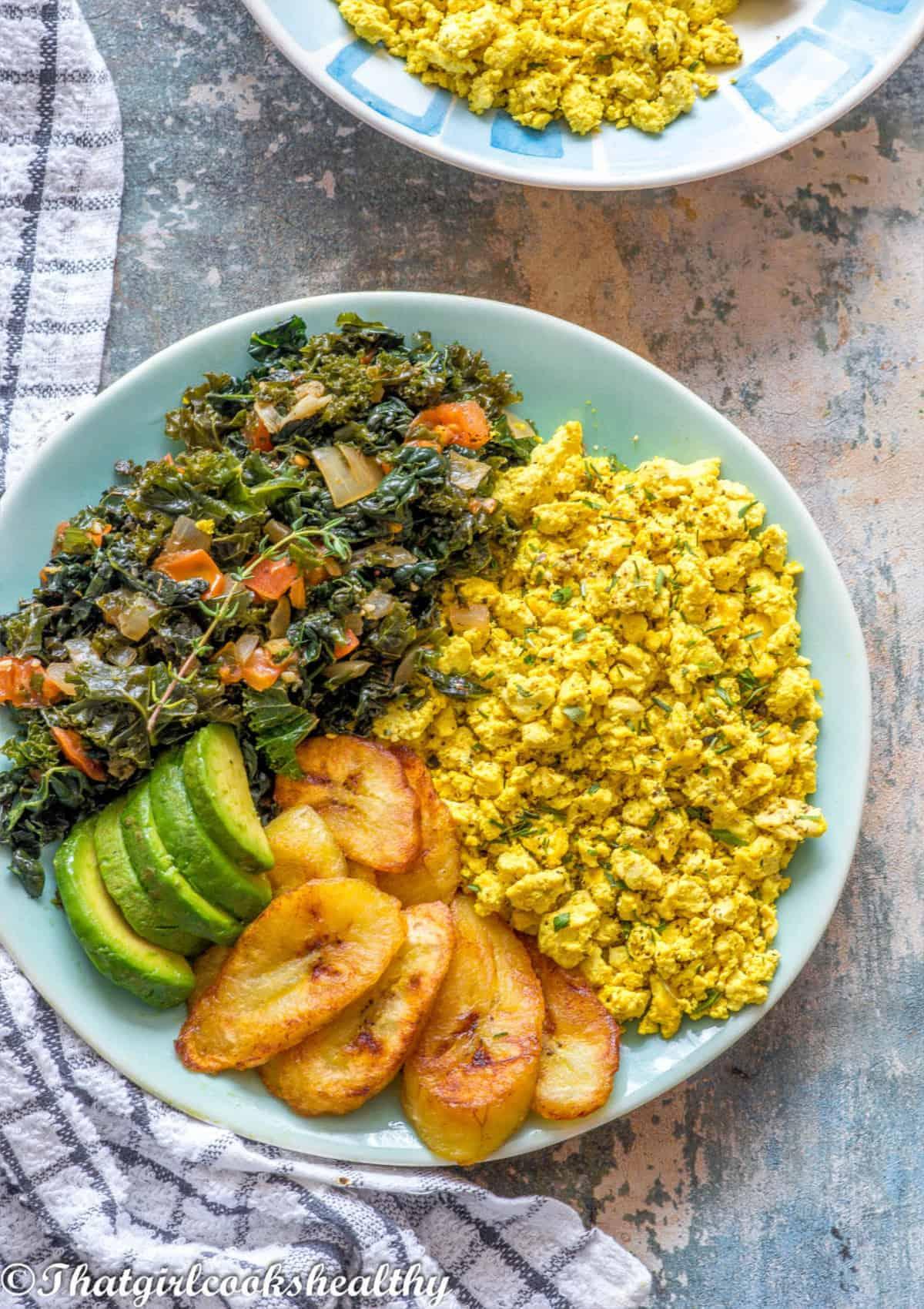 plate of scrambled tofu, plantain, avocado and greens
