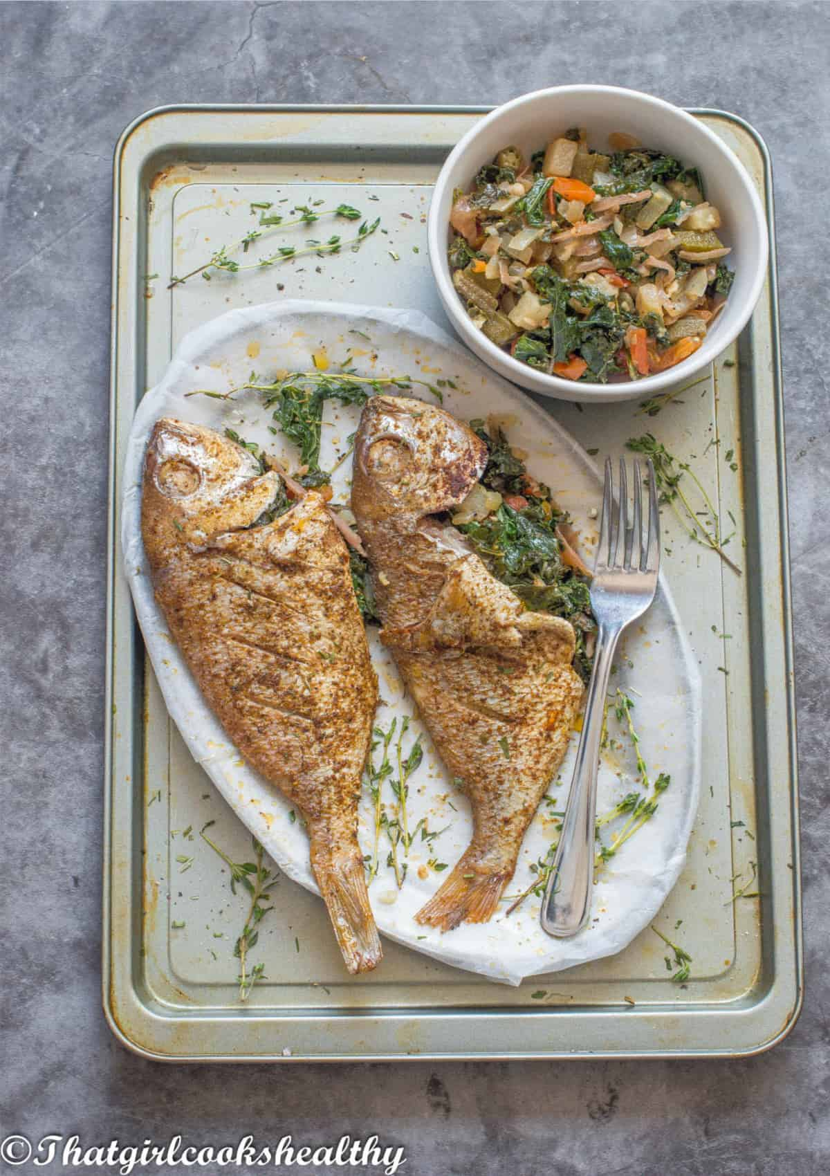2 fish on a tray with vegetables